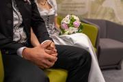 Brautpaar hält Hände bei der Trauung.